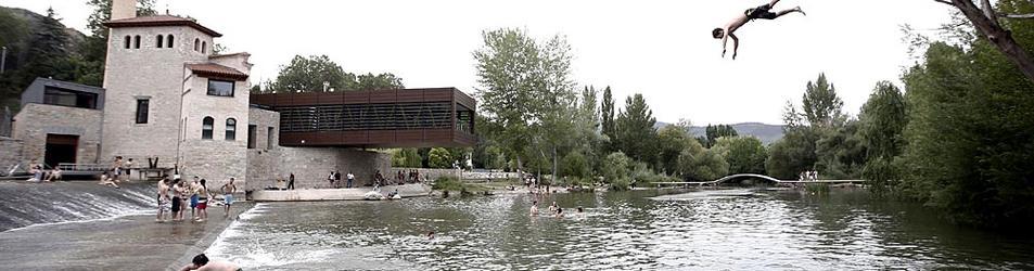 Varias personas se bañan en el río Arga a la altura del Molino de Caparroso en un día de calor en Pamplona