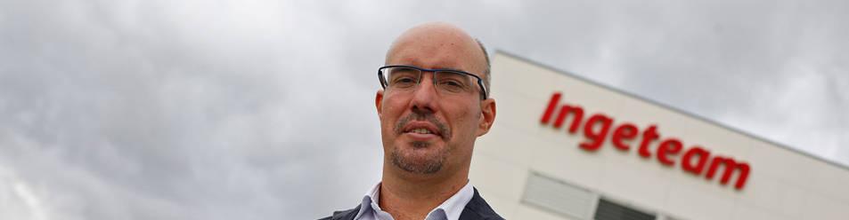 Jon Asín Muñoa posa con el enchufe de su coche eléctrico junto a los postes de carga rápida de su empresa Ingeteam en Sarriguren.