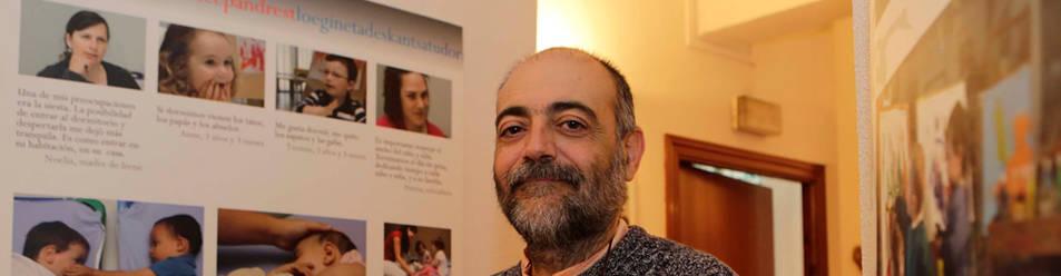 Alfredo Hoyuelos Planillo, en la sede del Organismo Autónomo de Escuelas Infantiles, junto a varios paneles con fotografías de actividades en distintas escuelas.