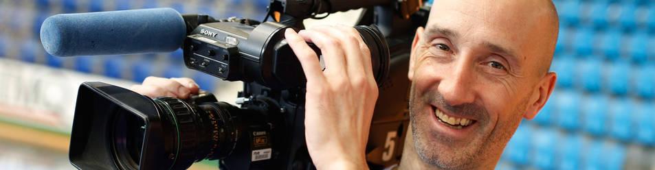 En la imange, un sonriente Javi Eseverri, con la cámara de televisión apoyada en su hombro, tras el entrenamiento de este martes en Anaitasuna.