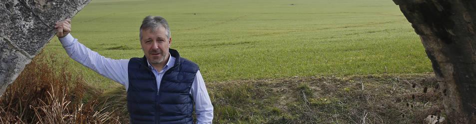 El presidente del sindicato UAGN, Félix Bariáin Zaratiegui, apoyado en un arco del acueducto de Noáin. Detrás, un campo de cereal recién brotado.