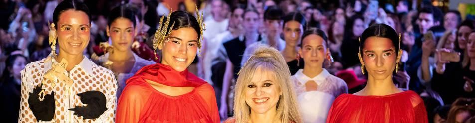 María Lafuente, en el centro con un ramo de flores, junto a las modelos de su último desfile.