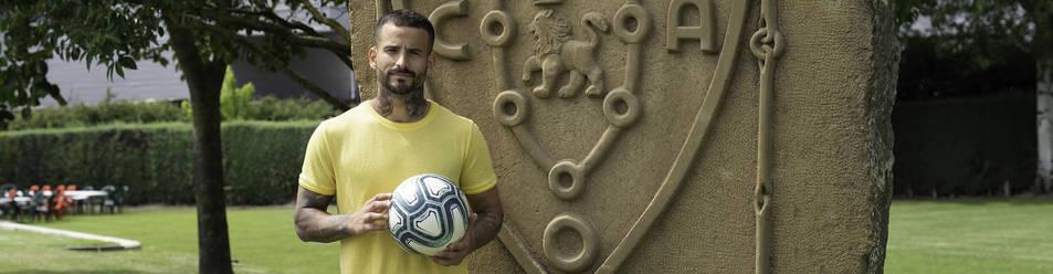 Foto de Rubén García posando junto al escudo de su equipo.