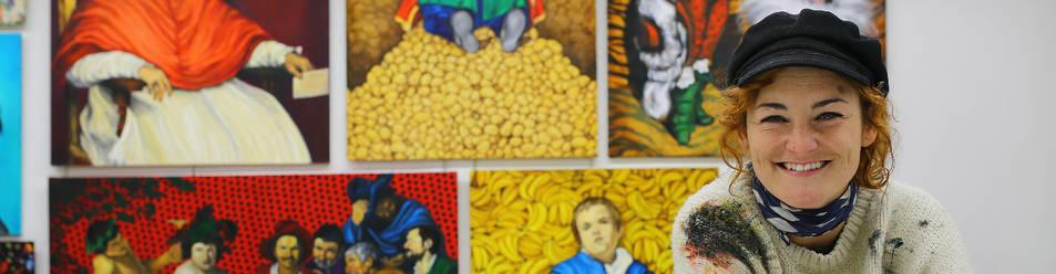 Foto de la artista Ana Pagola Divassón, frente a algunas de sus revisiones desenfadadas de la obra de Velázquez.
