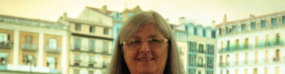 Foto de Nieves Tapia, de 62 años, delante de una fotografía de la Plaza del Castillo, en el hotel Maisonave.