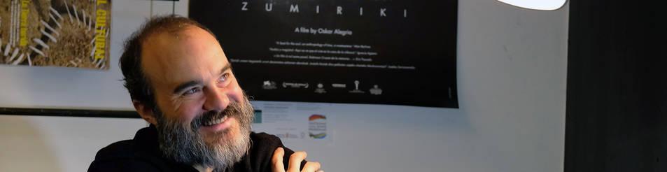 Foto de Oskar Alegria hace unos días en una cafetería de Pamplona. Al fondo, el póster de Zumiriki, con los árboles de la isla.