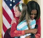 Una niña entrega a Michelle Obama el currículo de su padre