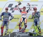 Marc Márquez celebra su triunfo acompañado en el podio por Jorge Lorenzo (i) y Valentino Rossi (d)