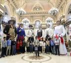 Personas disfrazadas colocan carteles en un tren turístico de San Sebastián