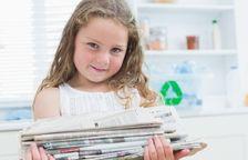Una niña lee un periódico.