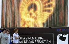 Tres mujeres pasan junto a una pantalla gigante de la 62 edición del Festival de Cine San Sebastián