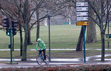 Un ciclista atraviesa la avenida Pío XII a la altura de la Vuelta del Castillo, bajo la lluvia.