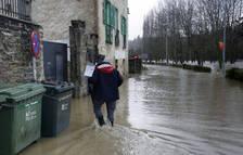 Una persona intenta llegar a su casa atravesando una zona anegada