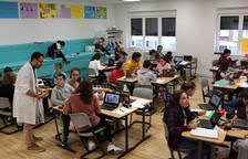 Mikel Ilundáin asesora a sus alumnos de 1º de ESO mientras otros dos docentes acompañan en los diferentes espacios. Al fondo, las gradas sirven para las exposiciones orales, escucha o trabajo libre con portátiles.