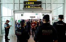 Agentes de los Mossos d'Esquadra y de la Policía Nacional controlan el acceso de personas a la terminal 1 del Aeropuerto de El Prat.
