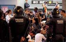 Agentes de los Mossos d'Esquadra controlan a los simpatizantes independentistas que han conseguido entrar en el T1 del Aeropuerto de El Prat.