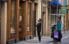 Foto de dos personas esperan a ser atendidas en una panadería del centro, respetando la distancia de seguridad.