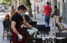 Foto de un camarero desinfectando una mesa tras las marcha de los clientes en la terraza de un bar.