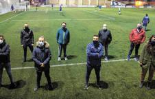 Los miembros de la junta directiva de la Unión Deportiva Mutilvera, en el campo de Mutilva, mientras al fondo entrena un equipo.