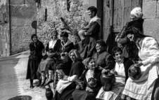 Grupo de mujeres de Lumbier portando vasijas en la puerta de una casa.