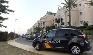 Un coche de la policia Nacional permanece a la entrada de la urbanización Lal Lomas de Sierra Blana de Marbella.