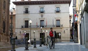Un vecino pasea en bici por la plaza Vieja, ante el ayuntamiento de la capital ribera.