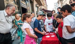 El joven aprendiz de mago Yago Torronteras  realizando un truco de cartas en la calle Tudela de Pamplona ayer por la mañana.