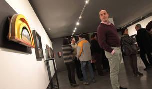 Joseja Casado mira una de las obras rodeado de asistentes