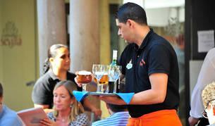 Un camarero atiende una mesa.
