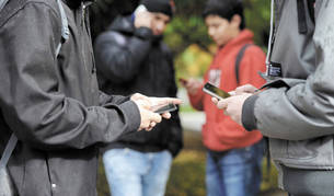 Un grupo de jóvenes pendientes de sus móviles.