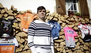 Pablo Urtasun, con los maillots que ha vestido como ciclista profesional durante 11 años (Csc, Kaiku, Liberty, Euskaltel, Ukyo y Funvic) junto a su casa en Urdiáin