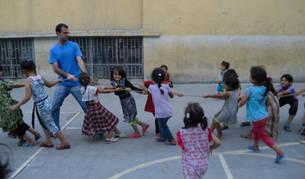 Un marista azul juega con niños y niñas refugiadas.