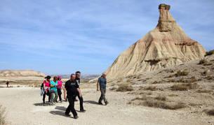 Un grupo de turistas pasea ante el emblemático cabezo de Castildetierrra del Parque Natural de Bardenas Reales de Navarra.