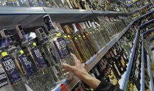 Mujer compra alcohol en un supermercado.