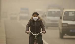 Joven china, protegida por una mascarilla, circula en bicicleta por una calle de Lanzhou, ciudad que sufre unos niveles altos de contaminación.