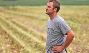 Un joven agricultor mira al cielo en un campo.