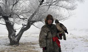 Un hombre perteneciente a la etnia manchú, la minoría más populosa de China, posa con su ave rapaz frente a un árbol cubierto de escarcha en la isla Wusongdao.