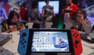 Varias personas jugando a videojuegos y una consola en primer plano.