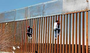 Imagen de dos niños subiendo el muro que separa México y Estados Unidos en Ciudad Juárez.