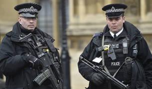 Dos policías hacen guardia frente a una puerta del parlamento londinense