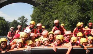 Niños y adolescentes se divierten sobre una piragua durante una actividad acuática en el campamento multiaventura en Bertiz-Narbarte, organizado por Aventura BKZ y patrocinado por Caja Rural.
