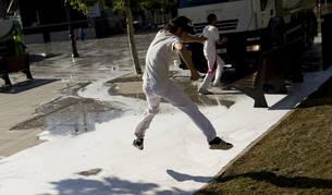 Foto de un joven saltando, ayer por la mañana, sobre un charco de agua y jabón mientras los operarios limpiaban en la Plaza del Castillo.