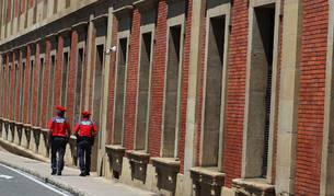 Dos agentes de la Policía Foral caminan junto al edificio del Parlamento de Navarra.