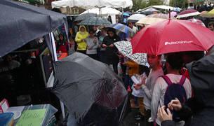 Los vecinos curiosean los puestos de artesanía mientras se resguardan de la lluvia bajo los paraguas.