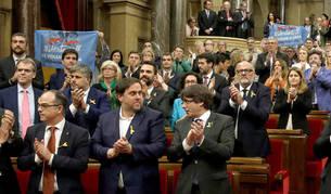 Imagen del presidente de la Generalitat, Carles Puigdemont (d) y el vicepresidente del Govern, Oriol Junqueras (2d), junto a los diputados de JxSí y la CUP tras aprobarse la declaración de independencia.