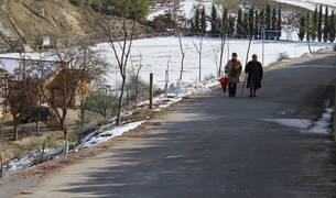 Foto de dos mujeres suben el paseo de la Paticuesta, donde ha comenzado a colocarse una valla de protección.