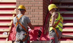 Dos trabajadores realizan tareas en un tejado