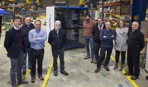 Representantes de las cuatro empresas que han cooperado en el proyecto de la fabricación de una nueva grúa.  Adrián Larripa (BigD), Raúl Musitu (Sumelec), Pascual Melero (Comansa),    Alfredo Ruiz (Teru), Farid Zeraibi (Sumelec), Iñaki Goñi (Teru), Javier Fernández (Comansa), Paula Iribarren (BigD) y Juan Carlos  Ruiz  (Teru) posan delante de las nuevas cabinas para grúas de construcción de Comansa, en las instalaciones de esta empresa en Huarte.