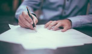 Imagen ilustrativa de un hombre escribiendo una reclamación