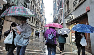 En la imagen, turistas paseando bajo la lluvia por el Casco Antiguo de Pamplona.